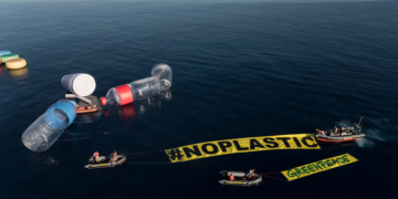 """Greenpeace's flagship, the Rainbow Warrior, has been surrounded by giant single-use plastic items in Mediterranean waters. The action seeks to make visible the invisible, and to denounce the problem of plastic pollution in the oceans, especially in the Mediterranean Sea.  Activists placed ten giant objects representing some of the most frequently found items on beaches: two bottles of 12 meters, two glasses of 6 meters and giant straws and bottle caps. A banner of 60 m2, reads #NoPlastic.  Approximately 40% of the demand of plastic in Europe is for plastic packaging, most of it single-use. Also plastic packaging is the most common waste littered in the environment round the world. This action is part of the international campaign """"Less plastic, more Mediterranean"""" in which the flagship of Greenpeace, Rainbow Warrior, is touring the Mediterranean to denounce the huge presence of plastic in the sea and to demand governments in the region to take urgent measures to stop this serious problem."""