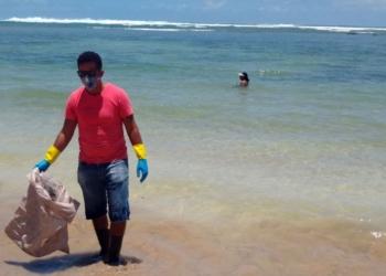 O voluntário Robério Nunes ajuda no trabalho de retirada de óleo de praia em Morro de São Paulo, na Bahia
